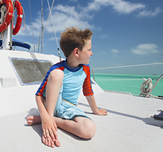 Boy on a boat in a swimsuit on the ocean